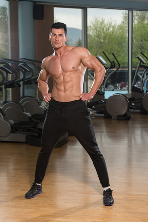 male male torso: Young Man Stretching Before Exercising In Fitness Center Healthy Lifestyle Concept