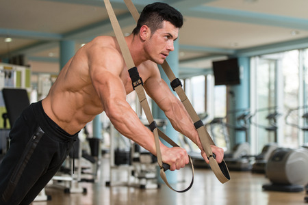 Attractive Man Does Crossfit Push Ups With Trx Fitness Straps In The Gyms Studio