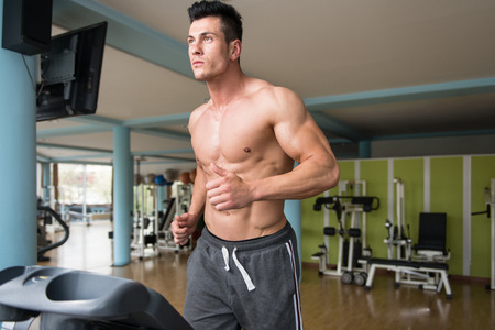 bel homme: Handsome Man Running On The Treadmill In Gym