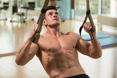 push: Attractive Man Does Crossfit Push Ups With Trx Fitness Straps In The Gyms Studio