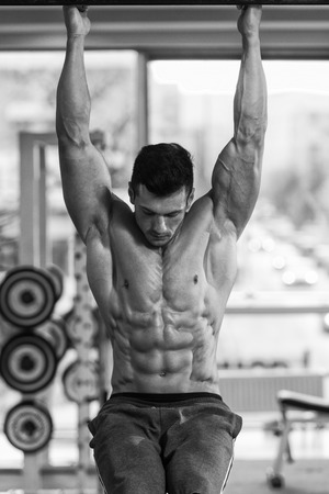 young adult men: Young Man Performing Hanging Leg Raises Exercise - One Of The Most Effective Ab Exercises