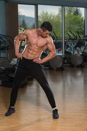 male model torso: Young Man Stretching Before Exercising In Fitness Center Healthy Lifestyle Concept