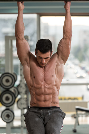 muscular body: Young Man Performing Hanging Leg Raises Exercise - One Of The Most Effective Ab Exercises