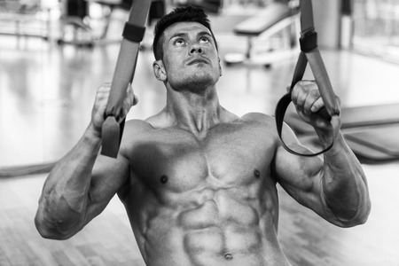 Attractive Man Does Crossfit Push Ups With Trx Fitness Straps In The Gym's Studio Stock Photo - 44727502