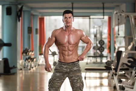 male model torso: Portrait Of A Physically Fit Young Man In Modern Fitness Center