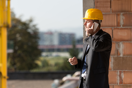 supervisor: Young Supervisor Talking On Mobile Phone And Smoking A Cigar Stock Photo