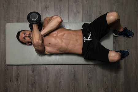 laying abs exercise: Healthy Athlete Exercising Triceps On Foor As Part Of Bodybuilding Training Stock Photo