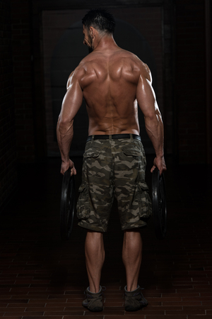 trapezius: Fit Athlete Working Out Trapezius With Weights