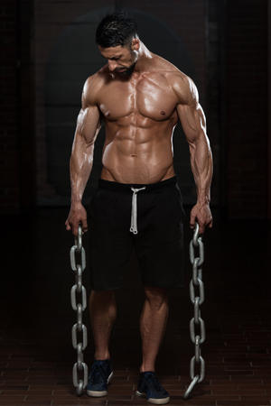 physically fit: Portrait Of A Physically Fit Man Showing His Well Trained Body And Holding Chains