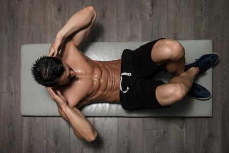hombre fuerte: Hombre sano ejercicio abdominales en Foor Foto de archivo