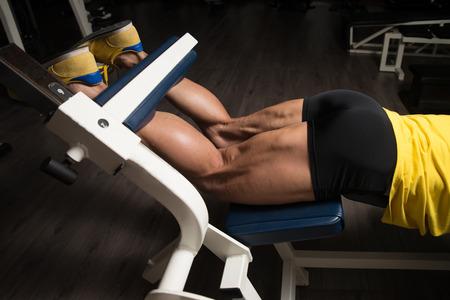 aerobics: Bodybuilder Doing Heavy Weight Exercise For Legs Hamstrings Stock Photo