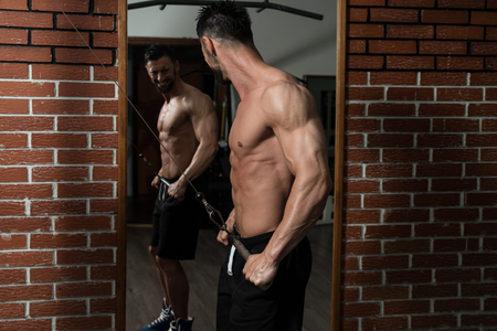 heavy weight: Bodybuilder Doing Heavy Weight Exercise For Back On Machine Stock Photo