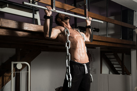 key chain: Bodybuilder Doing Heavy Weight Exercise For Back With Chains Stock Photo