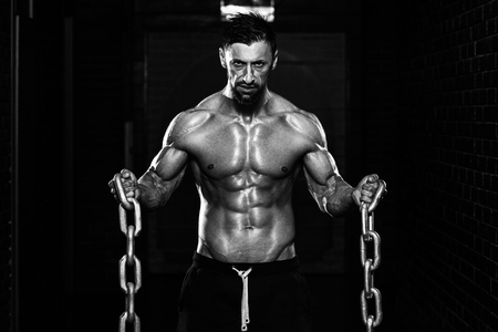 Healthy Bodybuilder Exercising Biceps With Chains