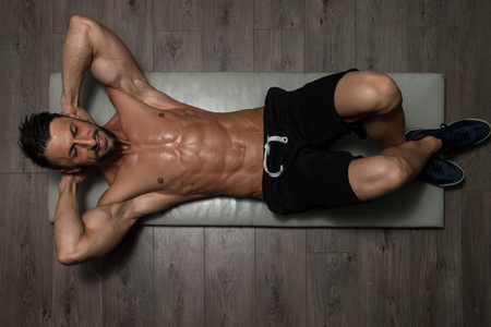 atleta: Healthy Man Exercising Abdominals On Foor