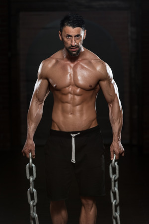 sexy abs: Portrait Of A Physically Fit Man Showing His Well Trained Body And Holding Chains