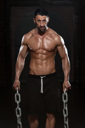 cadenas: Retrato de un hombre físicamente Fit Mostrando Sus Bien entrenado cuerpo y Agarrados Cadenas