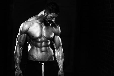Portrait Of A Befestigen Sie physikalisch Mann zeigt seine Gut ausgebildet Body And Holding-Ketten