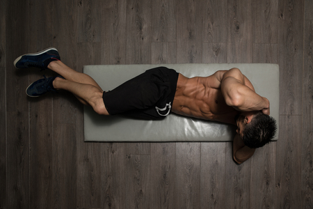 abdominals: Healthy Man Exercising Abdominals On Foor