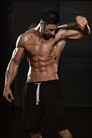 physically fit: Portrait Of A Physically Fit Man Showing His Well Trained Body And Holding A Hammer Stock Photo