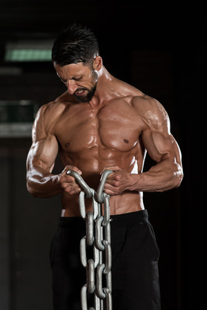 bodybuilding: Healthy Bodybuilder Exercising Biceps With Chains