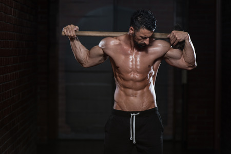 bodybuilding: Portrait Of A Physically Fit Man Showing His Well Trained Body And Holding A Hammer Stock Photo