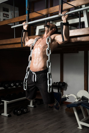 heavy chains: Bodybuilder Doing Heavy Weight Exercise For Back With Chains Stock Photo