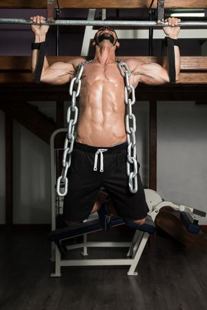beau jeune homme: Bodybuilder Faire Heavy Weight exercice pour le dos avec des cha�nes