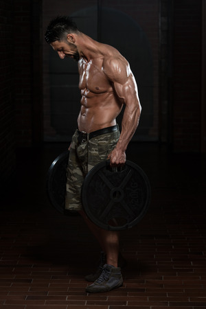 Fit Athlete Working Out Trapezius With Weights