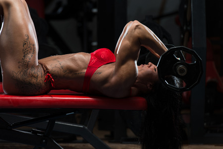 Young Woman In Underwear Doing Heavy Weight Exercise For Triceps With Barbell