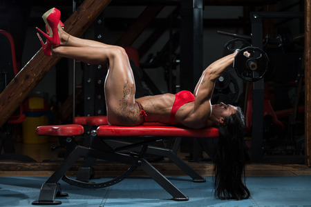 respite: Young Woman In Underwear Doing Heavy Weight Exercise For Triceps With Barbell