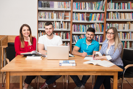 assignment: In The Library - Handsome Group Of Students With Laptop And Books Working In A High School - University Library - Shallow Depth Of Field