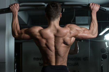 strong chin: Young Male Athlete Doing Pull Ups - Chin-Ups In The Gym Stock Photo
