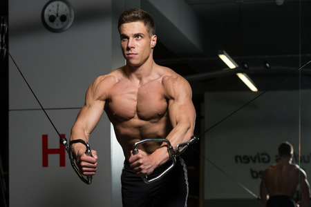 crossover: Young Bodybuilder Is Working On His Chest With Cable Crossover In A Dark Gym