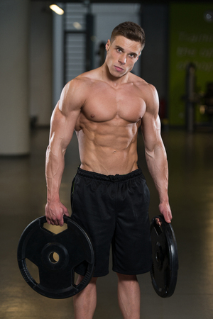 physically fit: Portrait Of A Physically Fit Man Holding Weights In Hand