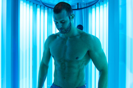 well build: Young Muscular Man At Solarium In Beauty Salon