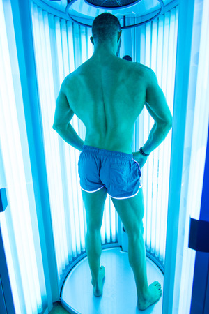 bodybuilding: Young Muscular Man At Solarium In Beauty Salon
