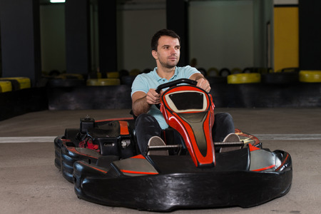 go kart: Young Man Is Driving Go-Kart Car With Speed In A Playground Racing Track - Go Kart Is A Popular Leisure Motor Sports