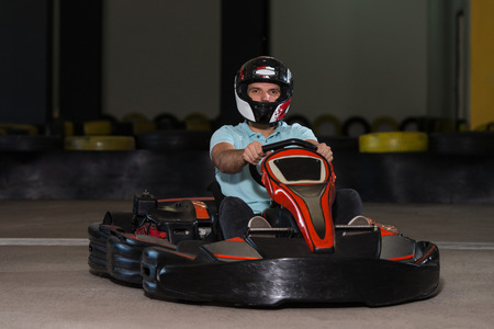 carting: Young Man Is Driving Go-Kart Car With Speed In A Playground Racing Track - Go Kart Is A Popular Leisure Motor Sports