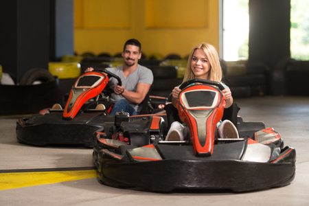 go kart: Group Of People Is Driving Go-Kart Car With Speed In A Playground Racing Track - Go Kart Is A Popular Leisure Motor Sports