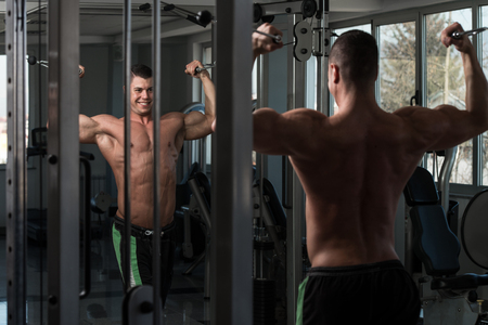 crossover: Young Bodybuilder Is Working On His Biceps With Cable Crossover In A Dark Gym