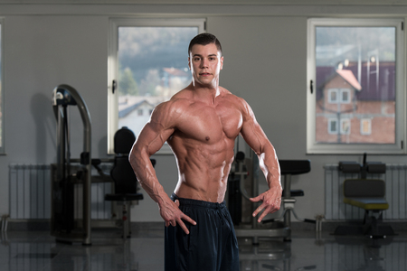 physically fit: Portrait Of A Physically Fit Man Showing His Well Trained Body In Gym