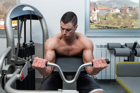 heavy weight: Young Athlete Doing Heavy Weight Exercise For Biceps On Machine