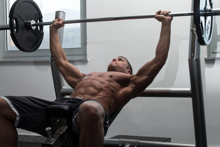 press: Young Man In Gym Exercising Chest On The Bench Press
