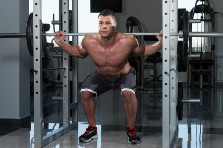 muscle boy: Young Man Performing Barbell Squats - One Of The Best Bodybuilding Exercise For Legs Stock Photo