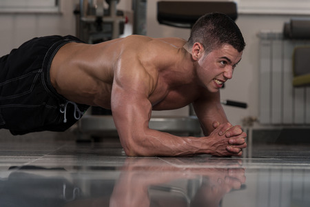 laying abs exercise: Healthy Young Man Exercising Abdominals On Foor