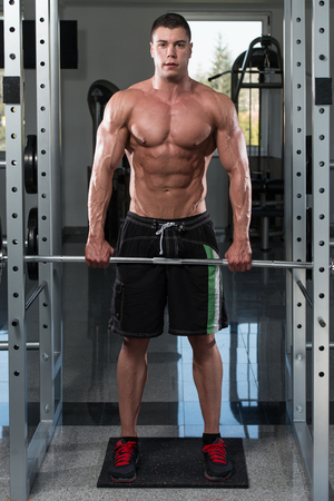 trapezius: Young Bodybuilder Is Working On His Trapezius With Barbell In A Gym