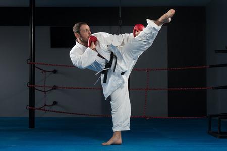 judo: Hombre joven que practica sus movimientos de karate - Blanco Kimono - Cinturón Negro