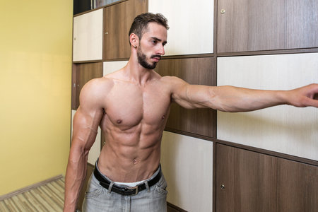muscular build: Muscular Build Athlete Changing In Gyms Locker Room And Having A Rest After Workout
