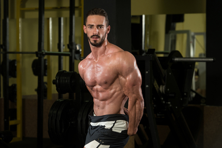 well build: Serious Man Standing Strong In The Gym And Flexing Muscles